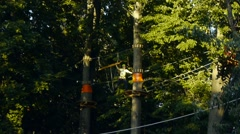 Man with insurance is on the high-altitude route in the ropes course Stock Footage