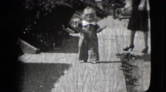 1942: a toddler eating ice-cream outdoor walking next to his mother in heels. Stock Footage