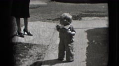 1942: a toddler outdoor attempting to walk before falling on butt NEW YORK Stock Footage