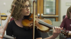 Close up of teenage girl playing violin in orchestra practice / American Fork, Stock Footage