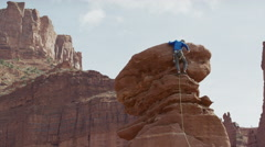 Wide low angle panning shot of man climbing rock formation / Fisher Towers, Stock Footage