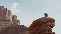 Wide low angle panning shot of man standing on rock formation / Fisher Towers, Stock Footage