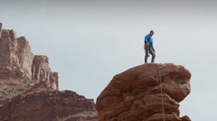 Wide low angle panning shot of man celebrating on rock formation / Fisher Stock Footage