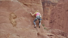 Wide shot of woman climbing on rock formation / Fisher Towers, Utah, United Stock Footage