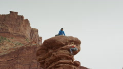 Wide low angle panning shot of couple climbing rock formation / Fisher Towers, Stock Footage