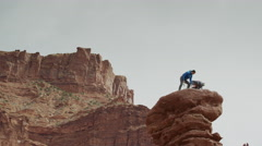 Wide low angle panning shot of couple celebrating on rock formation / Fisher Stock Footage