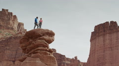 Wide low angle panning shot of couple standing on rock formation / Fisher Stock Footage