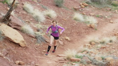 Wide slow motion high angle tracking shot of woman trail running in desert / Stock Footage