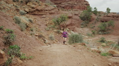 Wide slow motion shot of woman trail running in desert / Fisher Towers, Utah, Stock Footage
