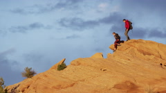 Wide panning tracking shot of couple hiking on rock formation / Moab, Utah, Stock Footage