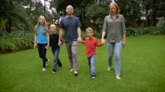 A little boy breaks free from his family and smiles as he approaches the camera Stock Footage