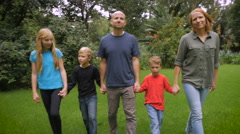 A happy smiling family look and walk towards the camera - slowmo steadicam Stock Footage