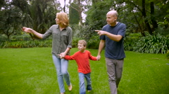 A mother and father hold hands with their son and point out things - slowmo Stock Footage