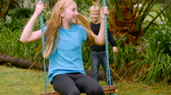 A young girl on a tree swing kicks her legs while a boy pushes her - slowmo Stock Footage