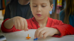 A young boy in red shirt playing with spinning tops on a table Stock Footage