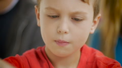 Close up of a young boy concentrating on playing a game at a table Stock Footage