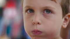 Close up of a cute young boy puffing up his cheeks like he is blowing in Slowmo Stock Footage