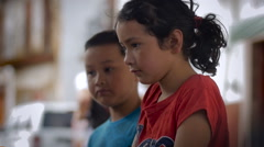 A young latin girl and boy talking and shrugging her shoulders - slowmo Stock Footage