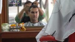 Female barber cut hair of caucasian man in Asian barbershop. Mirror reflection Stock Footage