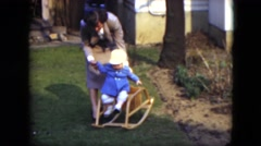 1951: baby try to stay on a little rocking chair with the help of an adult woman Stock Footage