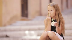 Adorable girl eating ice-cream outdoors at european city. Cute kid enjoying real Stock Footage