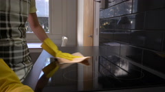 Housewife wipes the surface of the stove with a cleaning cloth. Dolly shot. Stock Footage