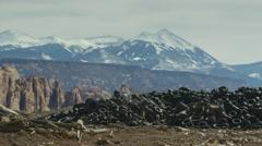 Wide panning shot of pile of tires in mountain range landscape / Moab, Utah, Stock Footage