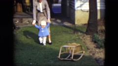 1951: mother helping a beautiful child to walk along the ground CLEVELAND, OHIO Stock Footage