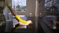 Housewife wipes the surface of the electric stove with a special cleaning cloth. Stock Footage