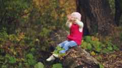 Baby in autumn park with yellow leaves Stock Footage