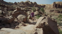 Wide slow motion low angle tracking shot of woman trail running in desert / Stock Footage
