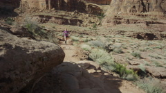 Wide panning shot of woman trail running in desert / Moab, Utah, United States Stock Footage