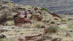 Wide slow motion shot of woman doing jumping jacks in desert / Moab, Utah, Stock Footage