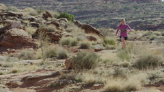 Wide tracking shot of couple trail running in desert / Moab, Utah, United States Stock Footage