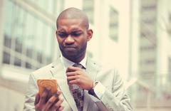 Unhappy young man talking texting on cellphone outdoors Stock Photos