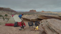 Wide panning shot of couple at campfire in desert / Moab, Utah, United States Stock Footage