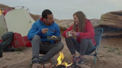Medium panning shot of couple at campfire in desert / Moab, Utah, United States Stock Footage