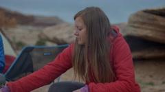 Medium panning shot of couple adding to campfire in desert / Moab, Utah, United Stock Footage