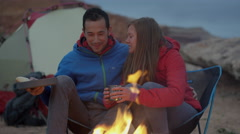 Medium panning shot of couple kissing at campfire in desert / Moab, Utah, United Stock Footage