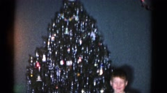 1962: a boy is standing in front of a christmas tree Stock Footage