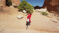 Wide low angle panning shot of couple hiking to desert arch / Arches National Stock Footage