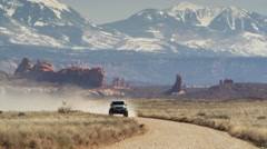 Wide shot of cars approaching on desert road / Arches National Park, Utah, Stock Footage