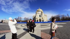 Teens take photo with sailor. Kronstadt Naval Cathedral in day on background Stock Footage