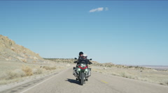 Wide tracking shot of couple riding motorcycle on desert road / Ferron, Utah, Stock Footage