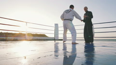 Two professional karate fighters are fighting on the beach boxing ring, slowmo Stock Footage