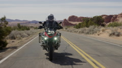 Medium tracking shot of man riding motorcycle on desert road / Arches National Stock Footage