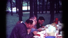 1964: people seated outdoor at a table enjoying a picnic CALIFORNIA Stock Footage
