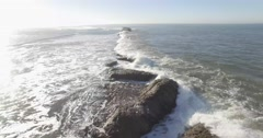 Aerial pull back shot over line of ocean rocks ending next to cliff in mornin Stock Footage