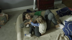 Medium high angle panning shot of mother tickling son on bed / Cedar Hills, Stock Footage