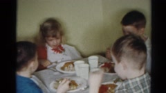 1964: four children are eating dinner together at their own table with plates Stock Footage
